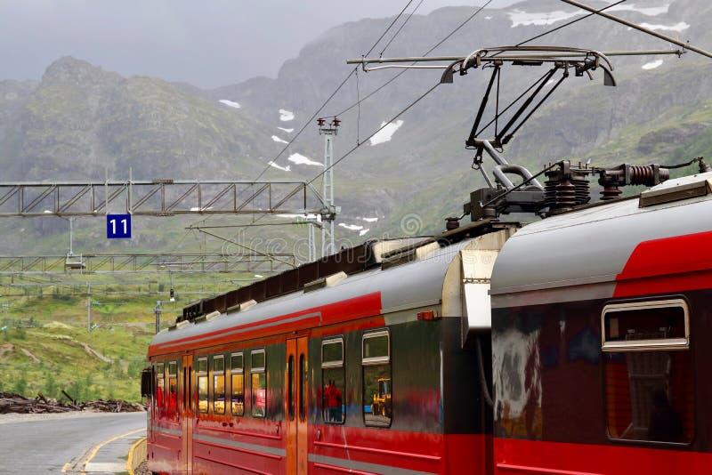 Vista del tren de la montaña de Voss parado en la estación de tren de Myrdal con los picos nevosos en el backgound, Noruega imagen de archivo libre de regalías