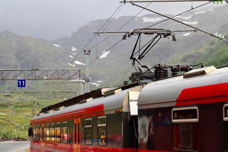 Vista del tren de la montaña de Voss parado en la estación de tren de Myrdal con los picos nevosos en el backgound, Noruega imagenes de archivo