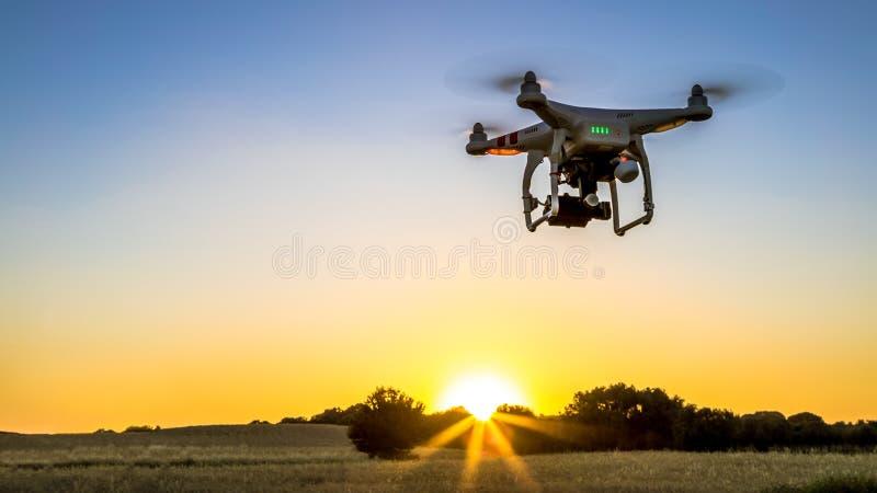 Vista del volo del fuco con la macchina fotografica digitale sopra un campo con il tramonto immagini stock libere da diritti