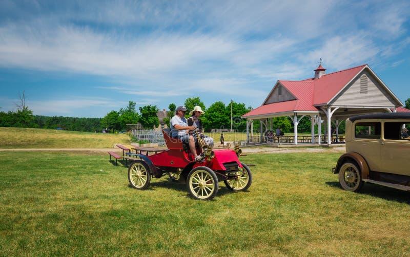 Vista delantera asombrosa del coche clásico viejo del vintage con la gente que conduce en parque foto de archivo libre de regalías