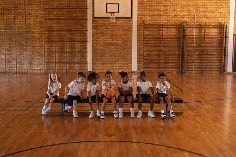Vista delantera de alumnos con el baloncesto que se sienta en banco en la cancha de básquet fotografía de archivo