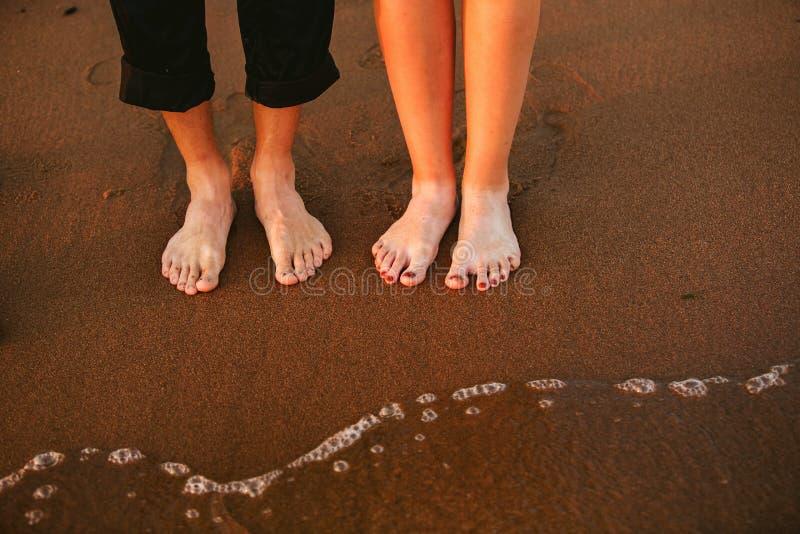 Vista delantera de casarse los pies del par que se colocan en la playa arenosa imágenes de archivo libres de regalías