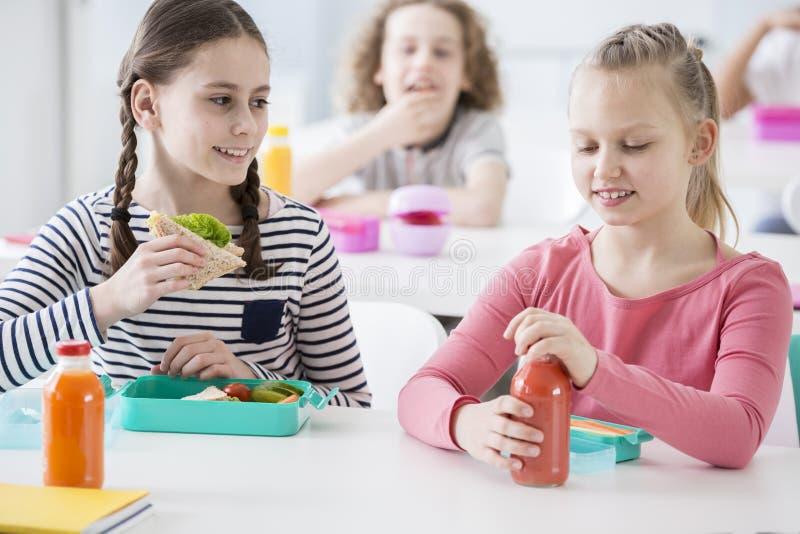 Vista delantera de dos muchachas menores en una cafetería de la escuela durante lunc fotos de archivo libres de regalías