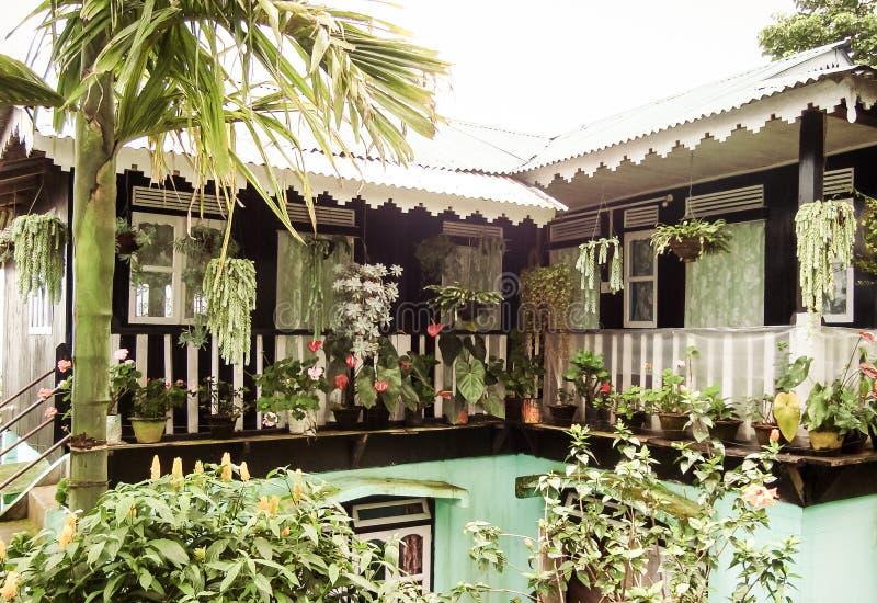 Vista delantera de la casa suburbana con el jardín de flores manicured Diseño hermoso del paisaje de decoración con los arbustos, imagen de archivo libre de regalías