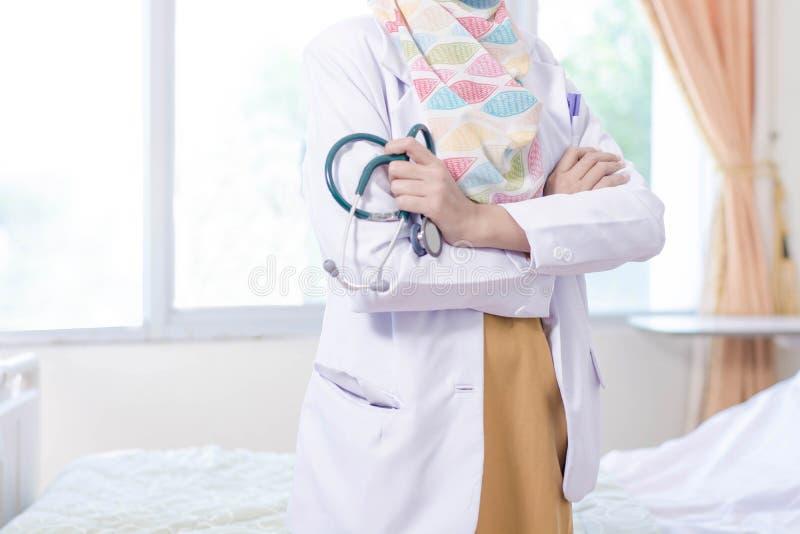 Vista delantera de la mano femenina del doctor del hijab que lleva a cabo el stetoschope dentro de un cuarto de la cama de hospit imágenes de archivo libres de regalías