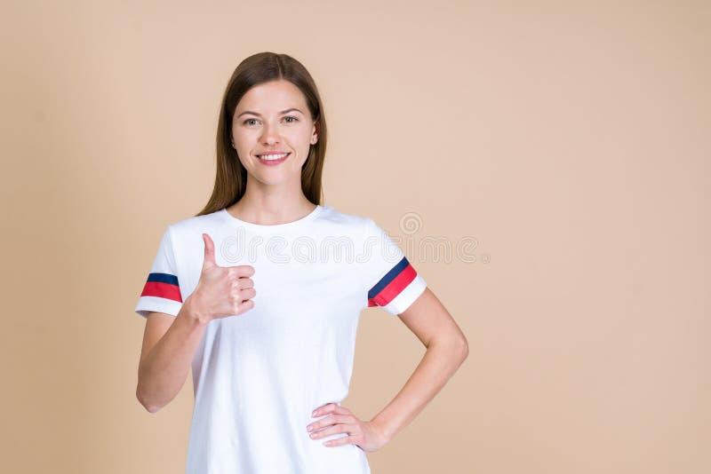 Vista delantera de la mujer adulta joven que sonríe, mirando la cámara y mostrando el pulgar para arriba foto de archivo libre de regalías