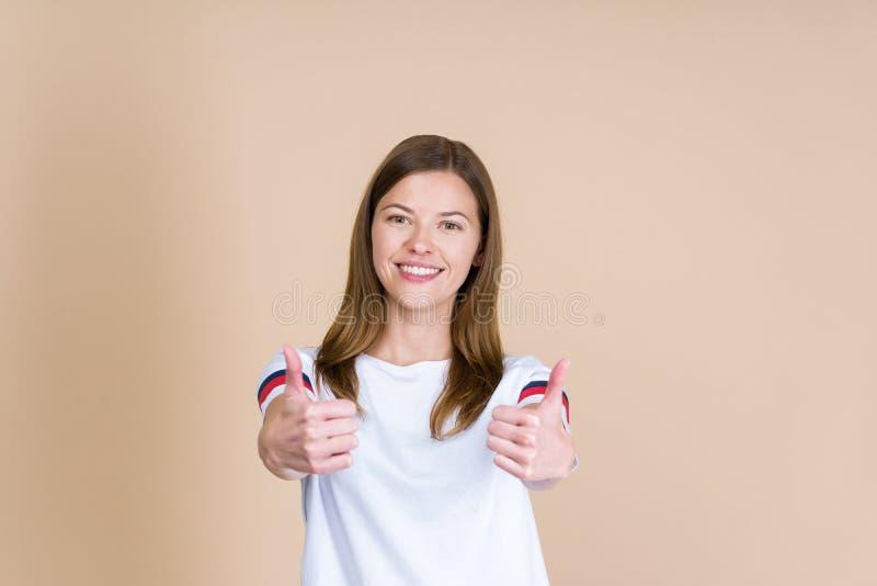 Vista delantera de la mujer adulta joven que sonríe, mirando la cámara y mostrando el pulgar para arriba en dos manos fotografía de archivo