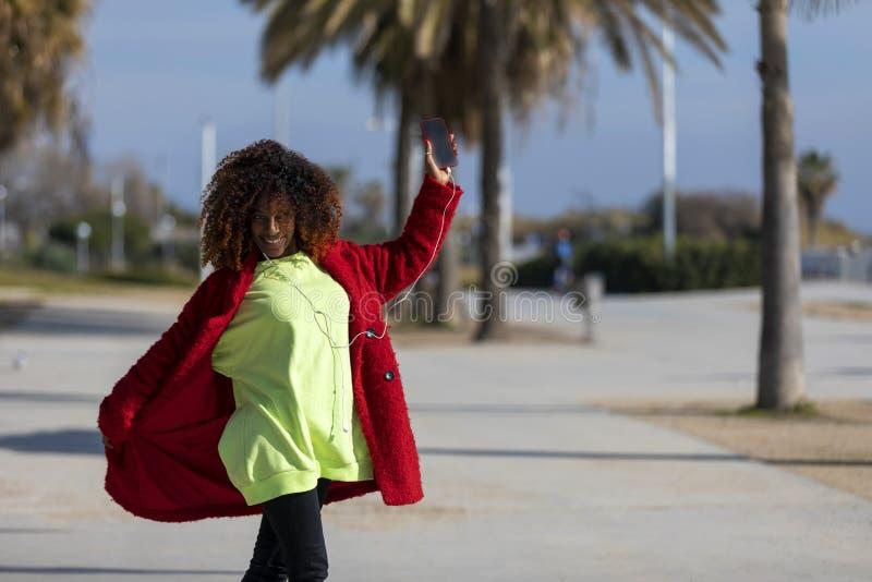 Vista delantera de la mujer afro rizada sonriente joven que se coloca al aire libre mientras que sonr?e y m?sica que escucha por  imagen de archivo libre de regalías