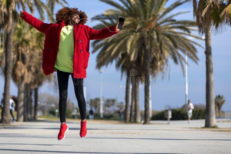 Vista delantera de la mujer afroamericana rizada hermosa joven que salta y que baila mientras que m?sica que escucha y que sonr?e imagen de archivo libre de regalías