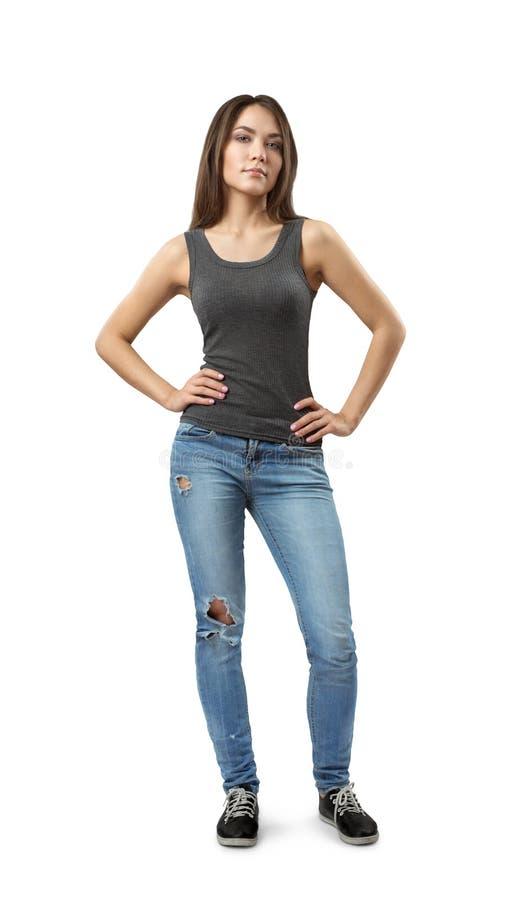 Vista delantera de la mujer hermosa joven en la situación gris de la blusa sin mangas y de los tejanos que mira la cámara con las imágenes de archivo libres de regalías