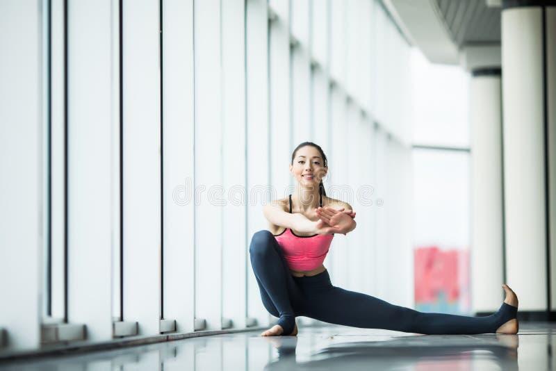 Vista delantera de la mujer joven hermosa en la ropa de deportes que hace estirar mientras que se sienta en el piso delante de la imagen de archivo libre de regalías