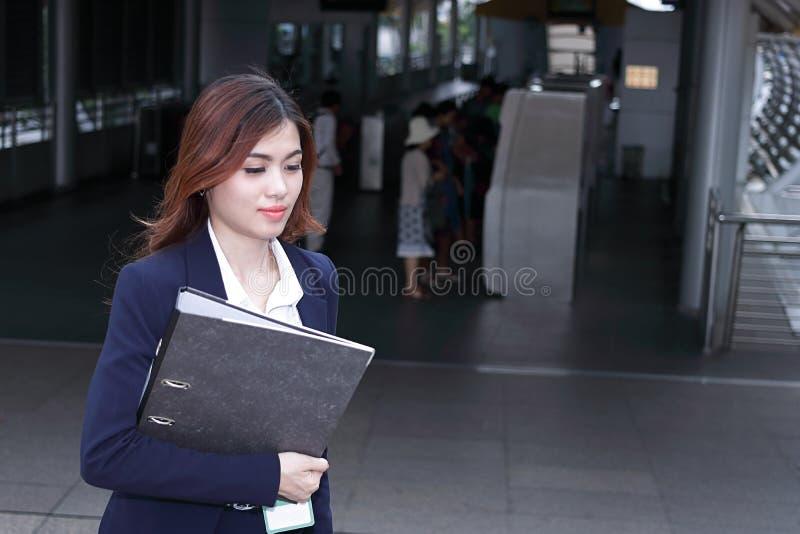 Vista delantera de la mujer de negocios asiática joven atractiva con la carpeta de anillo que camina encima de las escaleras en l imágenes de archivo libres de regalías