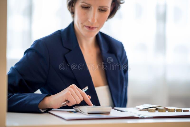 Vista delantera de la mujer de negocios bastante joven que se sienta detrás de su DES fotografía de archivo