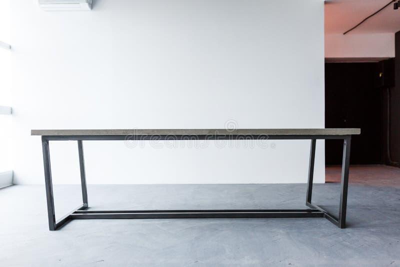Vista delantera de la tabla vacía en interior de la oficina en el fondo blanco de la pared diseño minimalistic del desván imagenes de archivo
