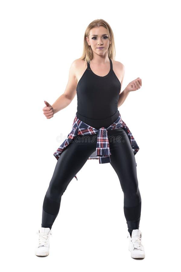 Vista delantera de los aeróbicos rubios atractivos de la danza del jazz del baile de la mujer que miran la cámara fotografía de archivo