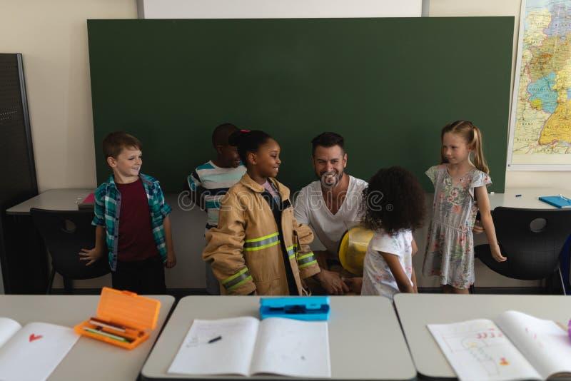 Vista delantera de los alumnos de enseñanza del bombero de sexo masculino sobre seguridad contra incendios en sala de clase fotos de archivo