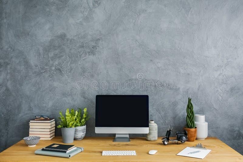 Vista delantera de un escritorio con un ordenador, las plantas, los cuadernos y moto imagenes de archivo