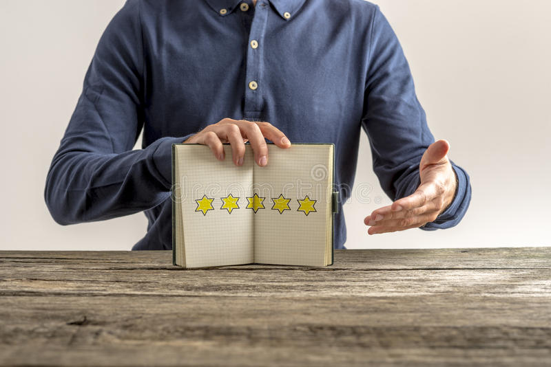Vista delantera de un hombre que presenta una libreta abierta con cinco de oro foto de archivo