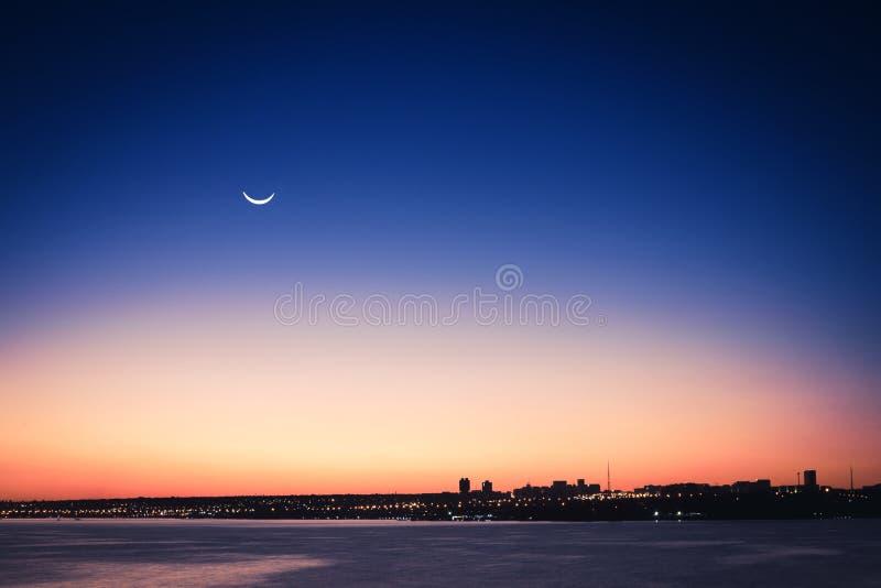 Vista delantera de un lago en una puesta del sol con la luna fotos de archivo libres de regalías
