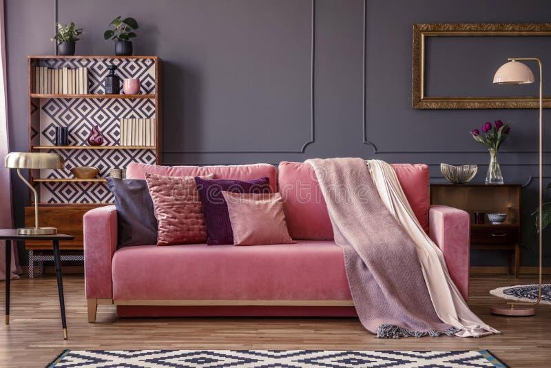 Vista delantera de un sofá rosado con las almohadas y la manta, cupb del vintage imágenes de archivo libres de regalías