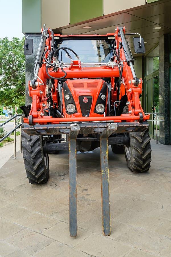 Vista delantera de un tractor multifuncional del nuevo Ursus rojo con la carretilla elevadora delantera fotos de archivo libres de regalías
