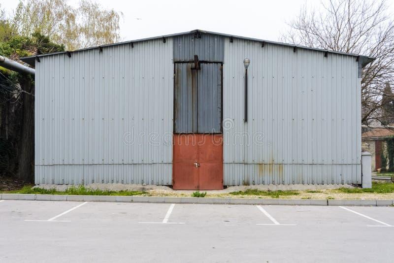 Vista delantera de una casa del almacenamiento del hierro cerca de un estacionamiento foto de archivo