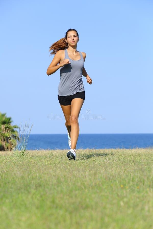 Vista delantera de una mujer hermosa que corre en la hierba imagenes de archivo