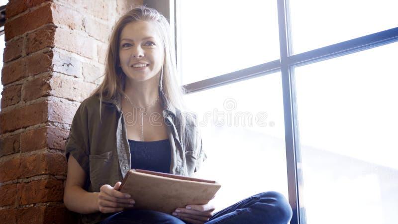 Vista delantera de una mujer joven que usa la tableta digital y sonriendo, tiro del retrato fotografía de archivo