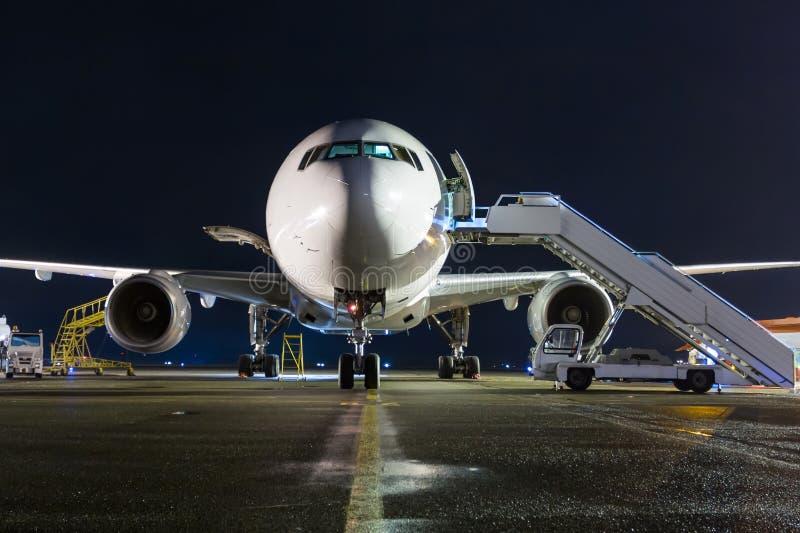 Vista delantera del aeroplano de fuselaje ancho blanco del pasajero con pasos de embarque en el delantal del aeropuerto de la noc imagenes de archivo