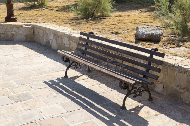 Vista delantera del banco marrón de madera en la acera en parque imagen de archivo libre de regalías