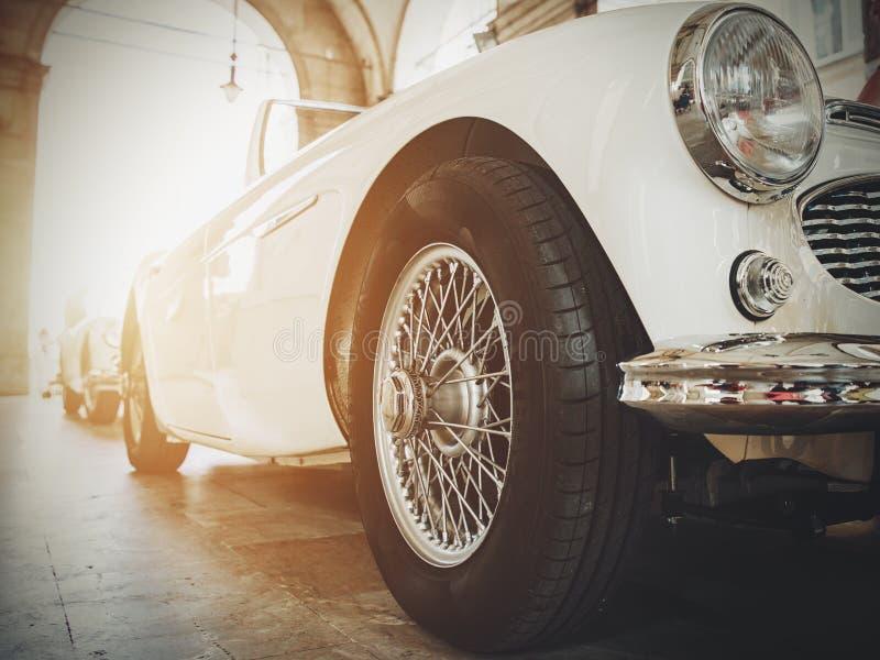 Vista delantera del coche clásico brillante blanco del vintage Postal entonada retra, cartel imágenes de archivo libres de regalías