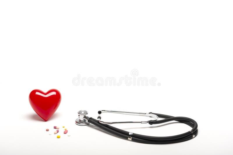 Vista delantera del corazón, de los estetoscopios, y de las drogas rojos plásticos en el fondo blanco imagenes de archivo