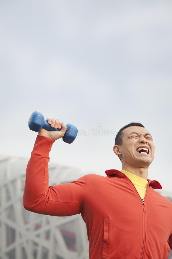 Vista delantera del hombre joven cansado en ropa atlética que ejercita con pesas de gimnasia en el parque, Pekín, China imagenes de archivo