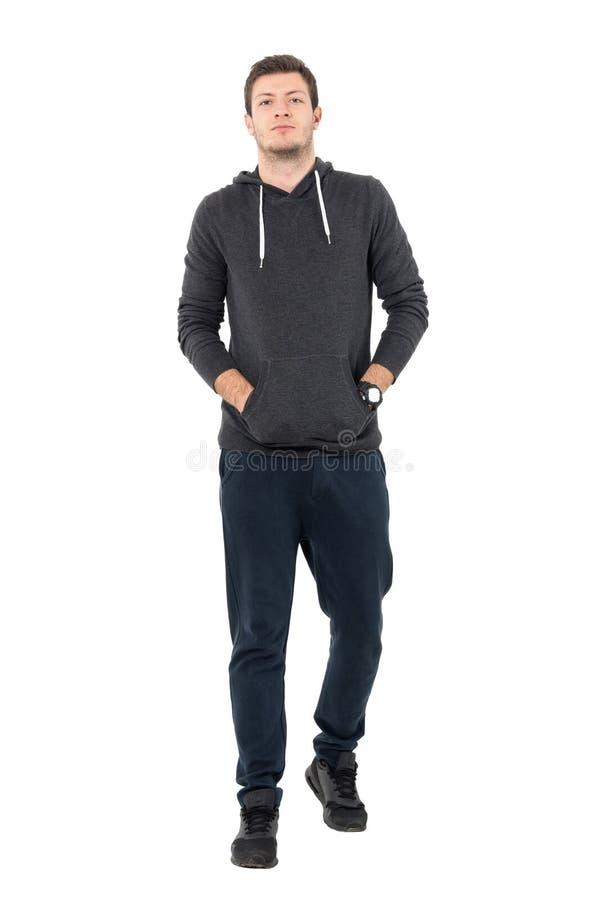 Vista delantera del hombre joven confiado en ropa de deportes que camina con las manos en bolsillos imagenes de archivo