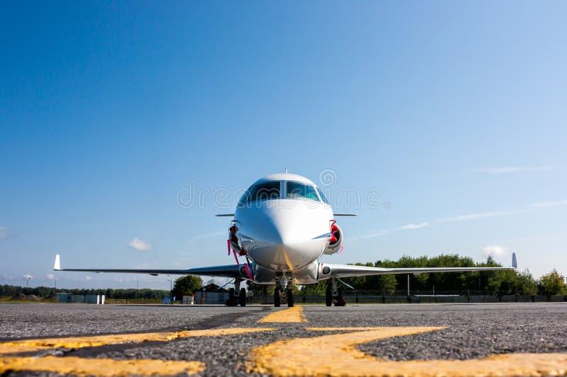 Vista delantera del jet blanco del asunto privado en el estacionamiento del aeropuerto fotografía de archivo