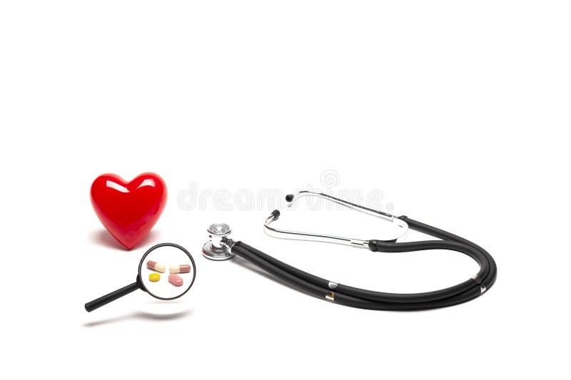 Vista delantera del modelo, de los estetoscopios, y de las drogas rojos plásticos del corazón con la lupa en el fondo blanco foto de archivo