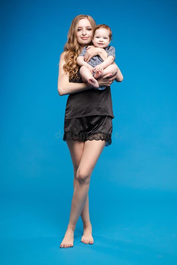 Vista delantera del pequeño bebé positivo que ríe con la madre foto de archivo