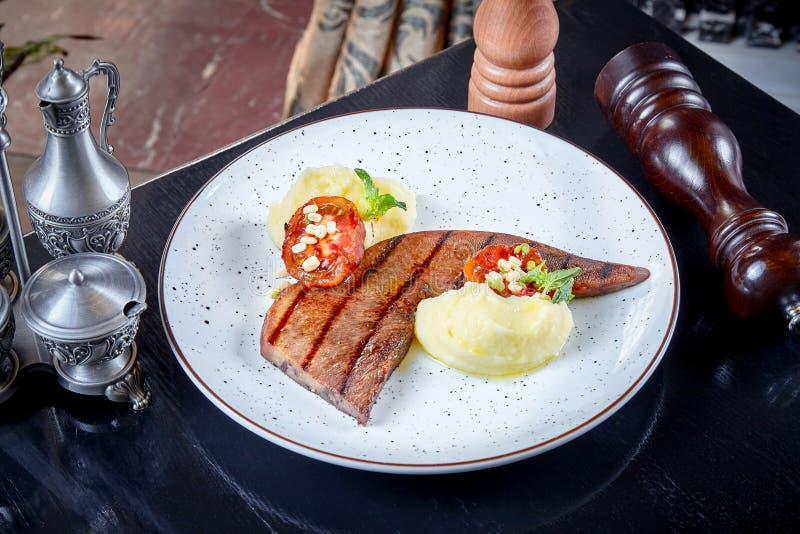Vista delantera sobre el filete de la lengua de carne de vaca con los purés de patata y el tomate asado a la parrilla servidos en imagen de archivo libre de regalías