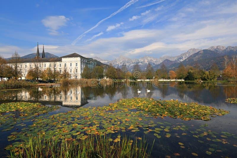 Vista dell'abbazia di Admont e dello stagno coperto di giglio un giorno soleggiato di autunno Admont, Austria immagine stock
