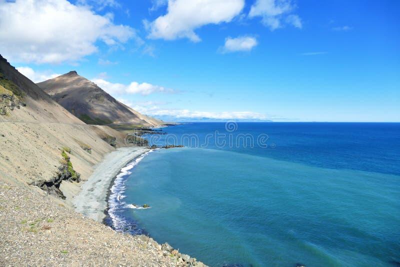 Vista dell'acqua e del litorale di mare blu intensi dell'Islanda alla luce solare luminosa fotografie stock