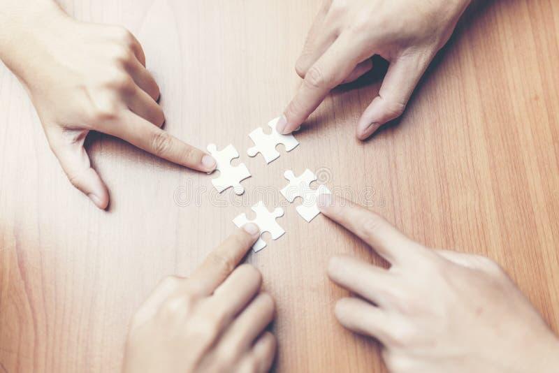 Vista dell'angolo alto della mano delle persone di affari che risolve puzzle sopra fotografia stock