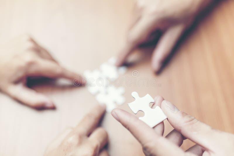 Vista dell'angolo alto della mano delle persone di affari che risolve puzzle sopra fotografie stock libere da diritti