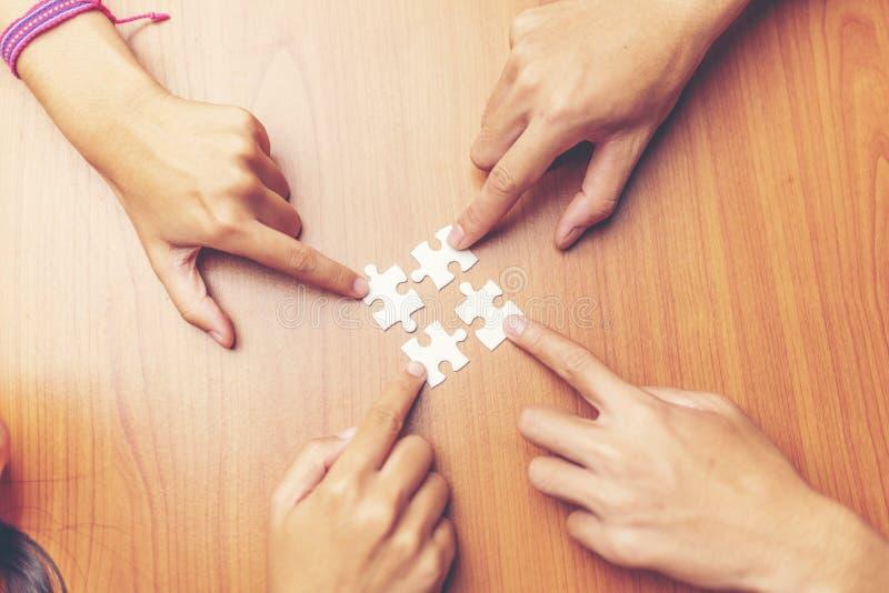 Vista dell'angolo alto della mano delle persone di affari che risolve puzzle sopra immagine stock libera da diritti