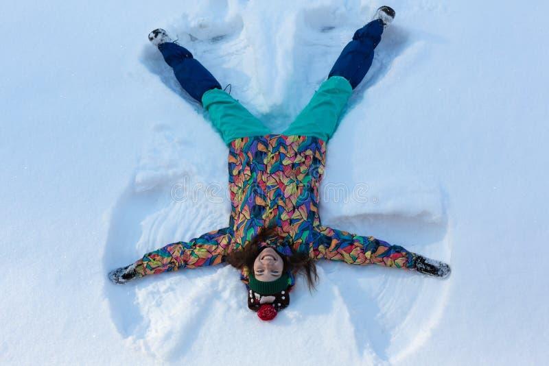 Vista dell'angolo alto della ragazza felice che si trova sulla neve e che muove le sue armi e delle gambe su e giù creare una fig fotografia stock libera da diritti