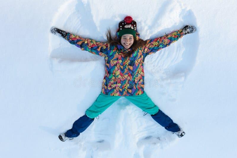 Vista dell'angolo alto della ragazza felice che si trova sulla neve e che muove le sue armi e delle gambe su e giù creare una fig immagine stock libera da diritti