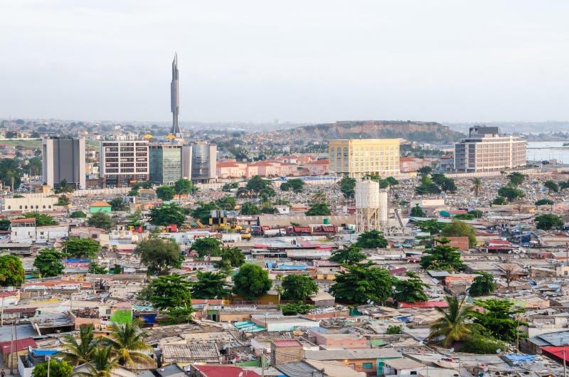 Vista dell'angolo alto sopra i bassifondi di Luanda con il mausoleo della torre di Agostinho Neto nel fondo, Angola, Africa immagini stock