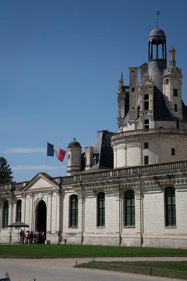 Vista dell'entrata di Chambord del castello con la bandiera francese fotografia stock