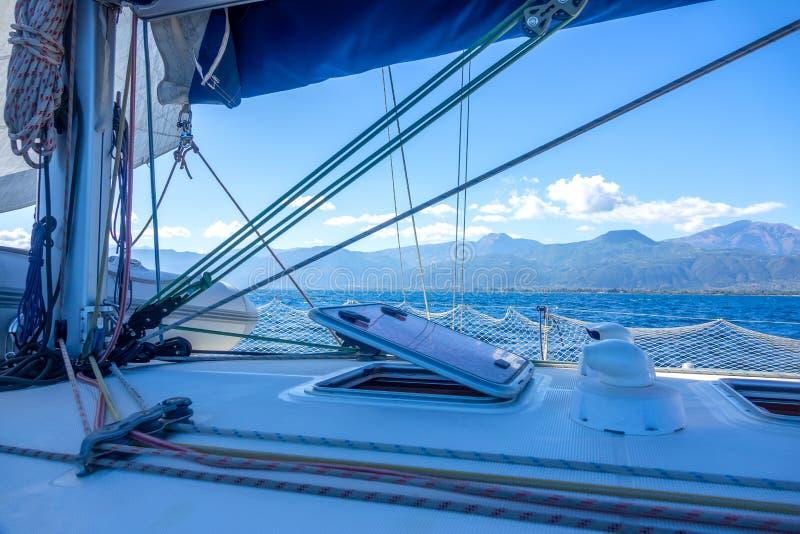 Vista dell'Hilly Coast Attraverso la manipolazione di uno Yacht a vela immagini stock libere da diritti