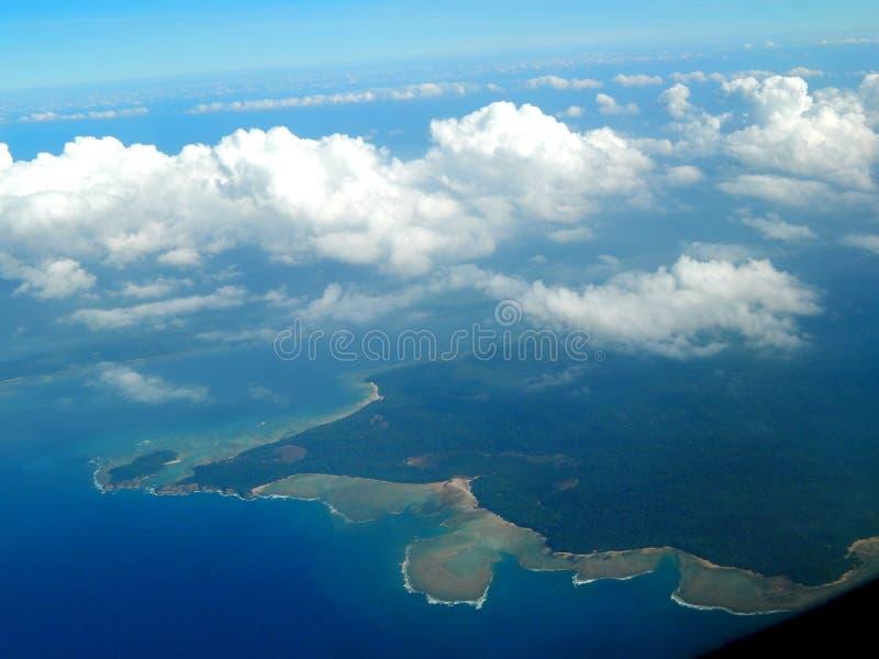 Vista dell'isola e delle nuvole insieme dall'aeroplano fotografia stock libera da diritti