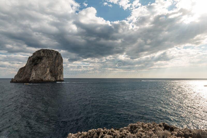 Vista dell'isola Italia di Capri, con alcune barche sull'acqua vicino a Faraglioni fotografia stock libera da diritti